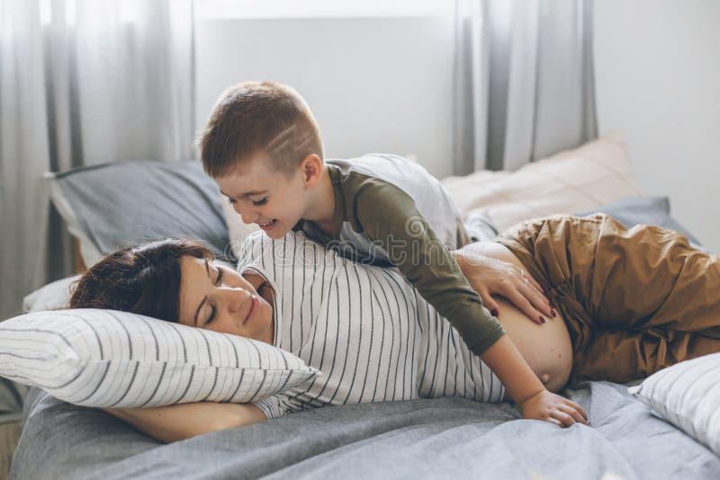 Έγκυος μητέρα που παίζει με παιδί στην κρεβατοκάμαρα στοκ φωτογραφία με δικαίωμα ελεύθερης χρήσης