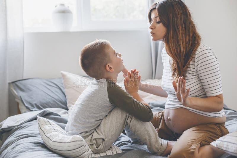 Έγκυος μητέρα που παίζει με παιδί στην κρεβατοκάμαρα στοκ εικόνα με δικαίωμα ελεύθερης χρήσης