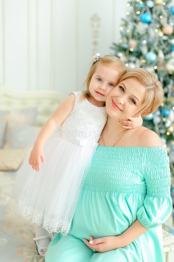 Έγκυος ξανθή μητέρα που φορά το μπλε φόρεμα και που αγκαλιάζει λίγη κόρη κοντά στο χριστουγεννιάτικο δέντρο στοκ φωτογραφίες με δικαίωμα ελεύθερης χρήσης