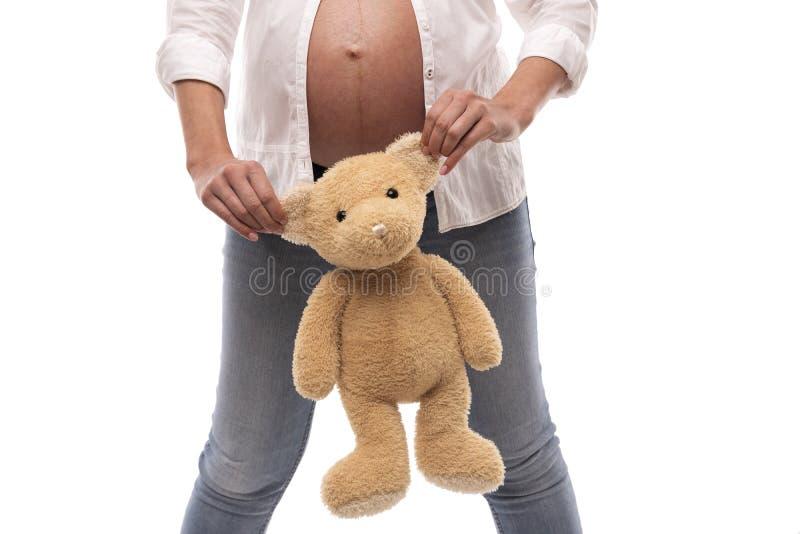 Έγκυο κορίτσι που κρατά μια teddy αρκούδα από τα αυτιά στο άσπρο υπόβαθρο στοκ εικόνα με δικαίωμα ελεύθερης χρήσης