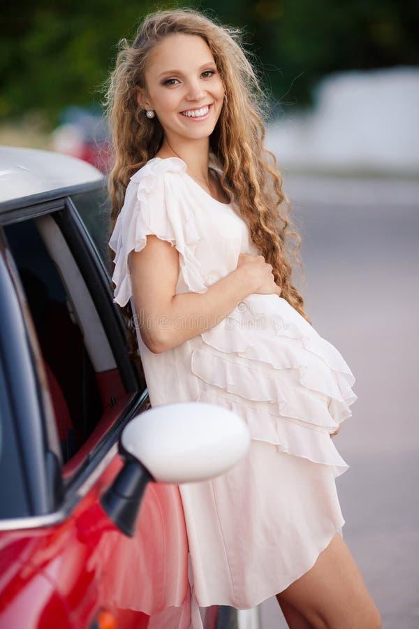 Έγκυο κορίτσι brunette και το κόκκινο αυτοκίνητό της στοκ εικόνα