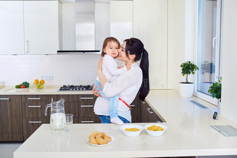 Έγκυο παιχνίδι μητέρων με την κόρη μικρών παιδιών στην κουζίνα στοκ φωτογραφία με δικαίωμα ελεύθερης χρήσης
