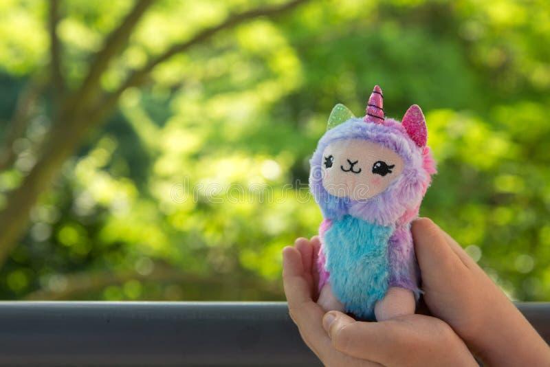 Έγχρωμος llama βελούδου μονόκερος στο μικρό κορίτσι χεριών με τα πράσινα στο υπόβαθρο στοκ φωτογραφία με δικαίωμα ελεύθερης χρήσης