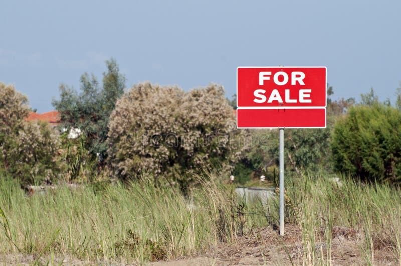 Έδαφος για το σημάδι πώλησης στον κενό τομέα στοκ φωτογραφίες
