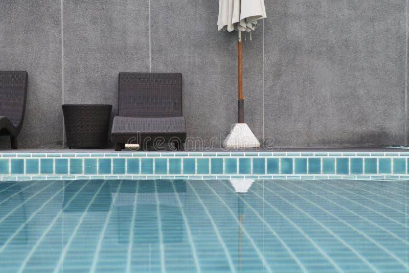 Έδρα και ομπρέλα που τίθενται εκτός από την πισίνα στοκ εικόνα
