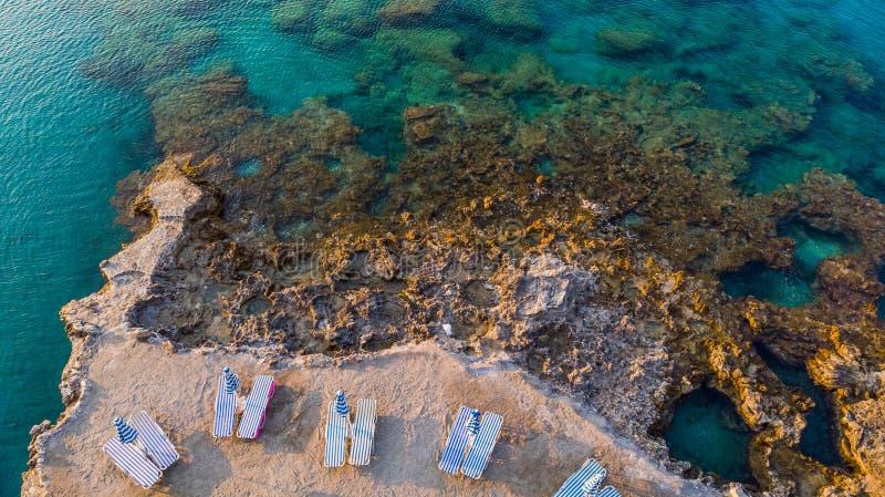 Έδρες στην παραλία από το τυρκουάζ νερό στο ελληνικό νησί, άποψη κηφήνων στοκ φωτογραφία με δικαίωμα ελεύθερης χρήσης