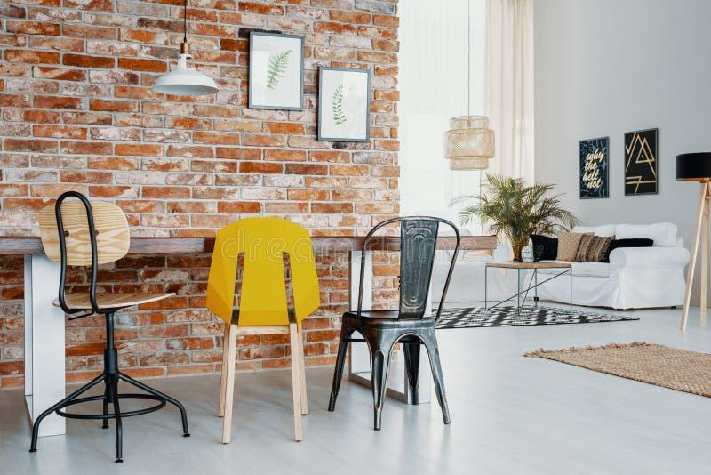Έδρες στον πίνακα ενάντια στον τούβλινο τοίχο με τις αφίσες στο σύγχρονο εσωτερικό διαμερισμάτων με το λαμπτήρα Πραγματική φωτογρ στοκ φωτογραφία με δικαίωμα ελεύθερης χρήσης