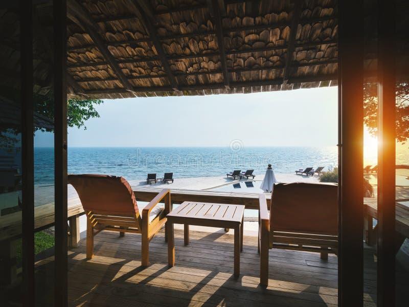 Έδρες στο πεζούλι με την όμορφη άποψη θάλασσας κατά τη διάρκεια του ηλιοβασιλέματος, έννοια θερινών διακοπών στοκ φωτογραφία