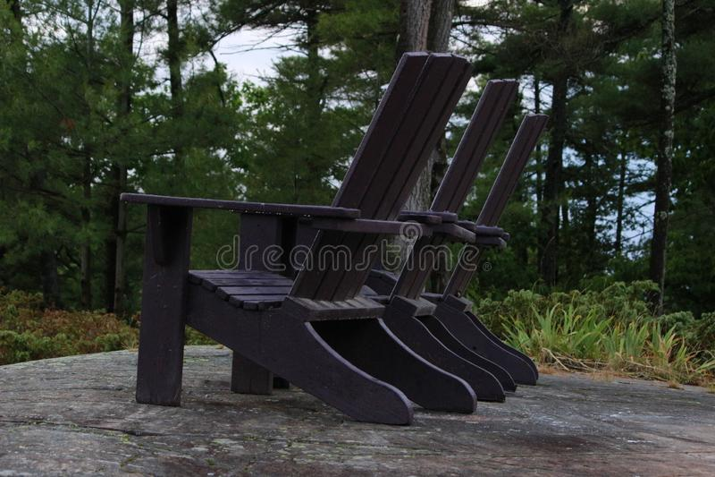 Έδρες Muskoka ή Adirondack στο τέλος μιας αποβάθρας που αγνοεί μια μεγάλη μπλε  στοκ εικόνες με δικαίωμα ελεύθερης χρήσης