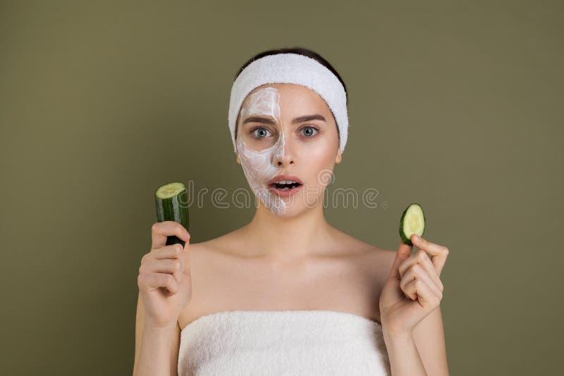 Έκπληκτη γυναίκα με τους γυμνούς ώμους που στη κάμερα με το ανοικτό στόμα, άσπρη μάσκα στο μισό από το πρόσωπό της στοκ φωτογραφία