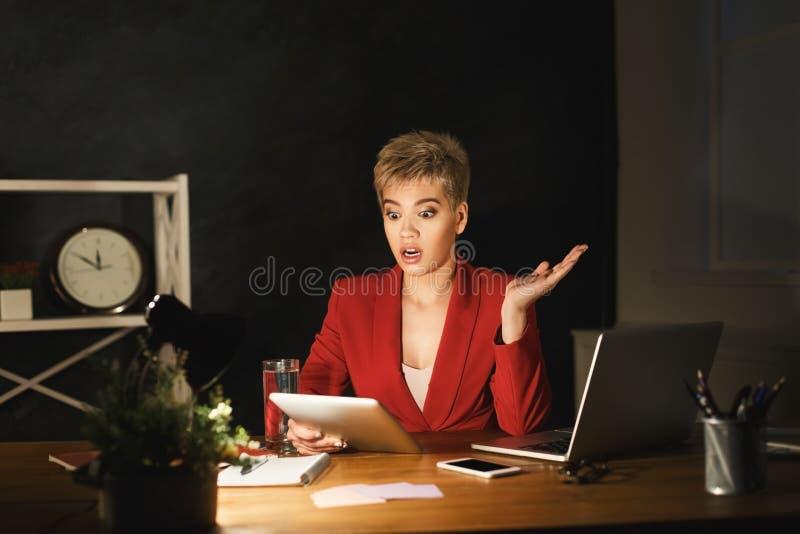 Έκπληκτη γυναίκα που εργάζεται στην ταμπλέτα αργά τη νύχτα στο γραφείο στοκ εικόνα με δικαίωμα ελεύθερης χρήσης