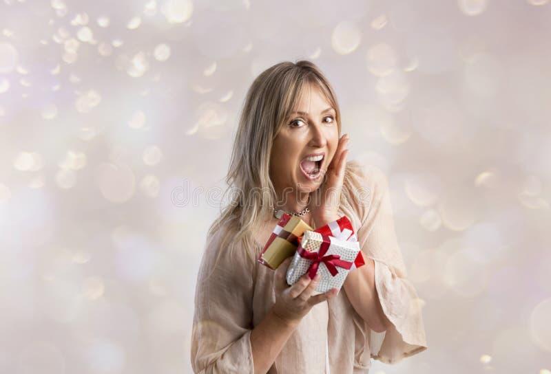 Έκπληκτη γυναίκα που κρατά μερικά δώρα Χριστουγέννων στοκ φωτογραφίες