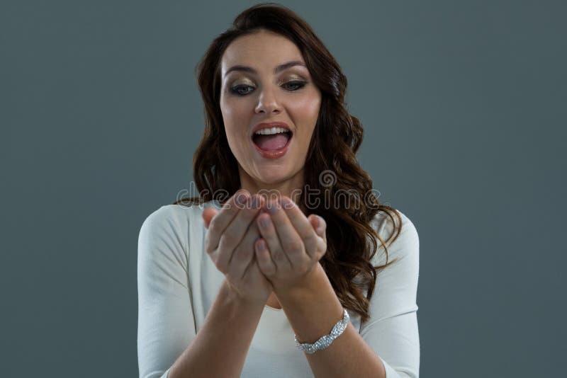 Έκπληκτη γυναίκα που στέκεται και που εξετάζει τα κοίλα χέρια της στοκ φωτογραφίες με δικαίωμα ελεύθερης χρήσης