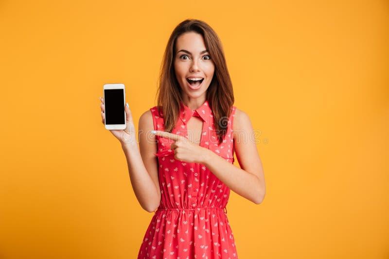 Έκπληκτη ευτυχής γυναίκα brunette στο φόρεμα που παρουσιάζει κενή οθόνη smartphone στοκ εικόνα