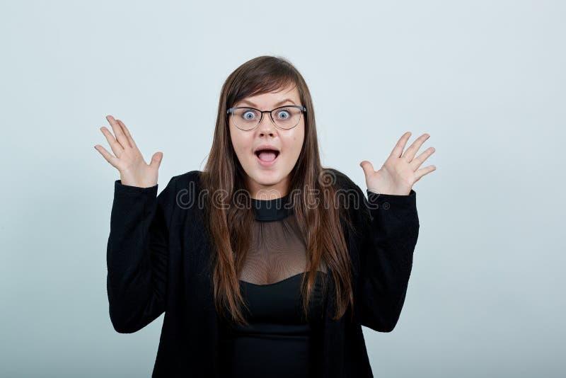 Έκπληκτη νεαρή γυναίκα άνοιξε το στόμα, απλώνοντας χέρια στοκ φωτογραφίες