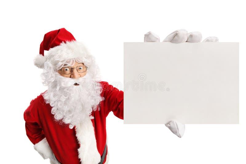 Έκπληκτος Άγιος Βασίλης που κρατά μια κενή κάρτα στοκ εικόνες