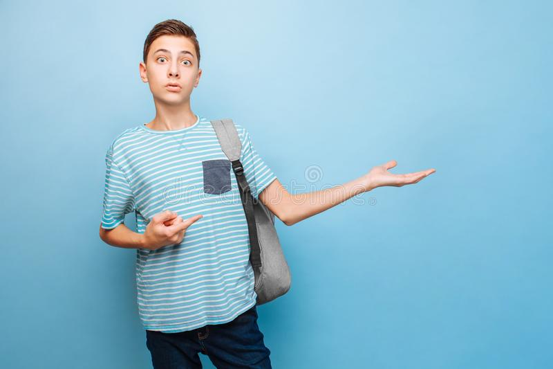 Έκπληκτος έφηβος που εξετάζει τη κάμερα, που δείχνει τα δάχτυλα σε ένα κενό διάστημα στοκ εικόνα