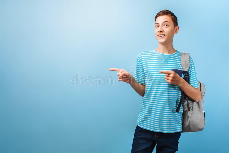 Έκπληκτος έφηβος που εξετάζει τη κάμερα, που δείχνει τα δάχτυλα σε ένα κενό διάστημα στοκ φωτογραφίες