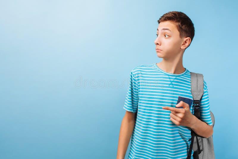 Έκπληκτος έφηβος που εξετάζει τη κάμερα, που δείχνει τα δάχτυλα σε ένα κενό διάστημα στοκ εικόνα με δικαίωμα ελεύθερης χρήσης