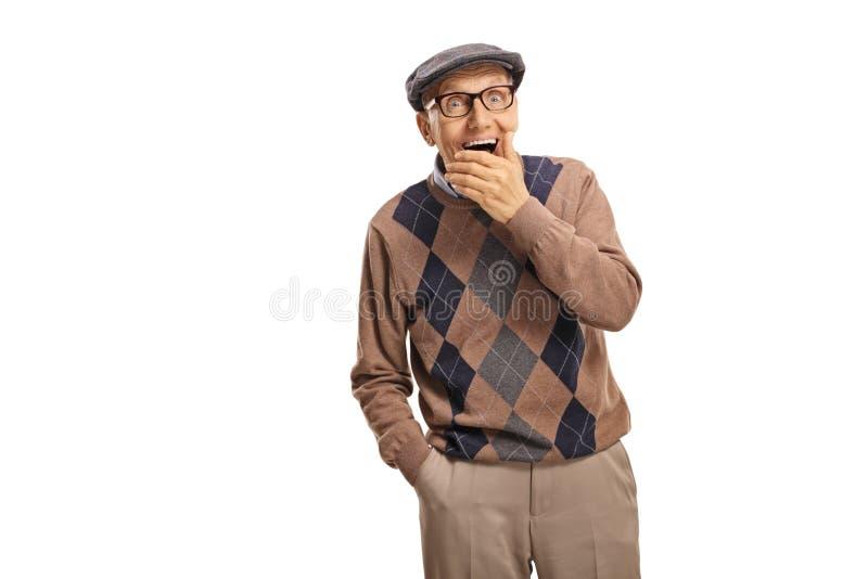 Έκπληκτος ανώτερος άντρας κρατά το στόμα του στοκ εικόνες