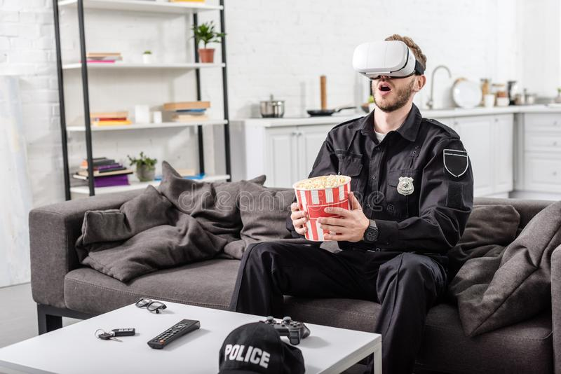 έκπληκτος αστυνομικός με την κάσκα εικονικής πραγματικότητας στον επικεφαλής popcorn εκμετάλλευσης ριγωτό κάδο και τη συνεδρίαση στοκ φωτογραφίες