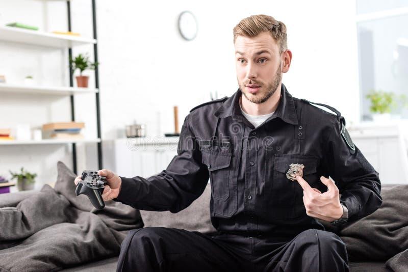 έκπληκτος αστυνομικός που παίζει το τηλεοπτικές παιχνίδι και την υπόδειξη στοκ φωτογραφία με δικαίωμα ελεύθερης χρήσης