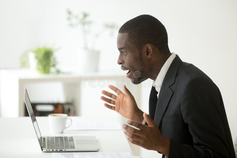 Έκπληκτος αφροαμερικάνος που εξετάζει το lap-top που μένει καταπληκτικό με την επιχείρηση στοκ φωτογραφία