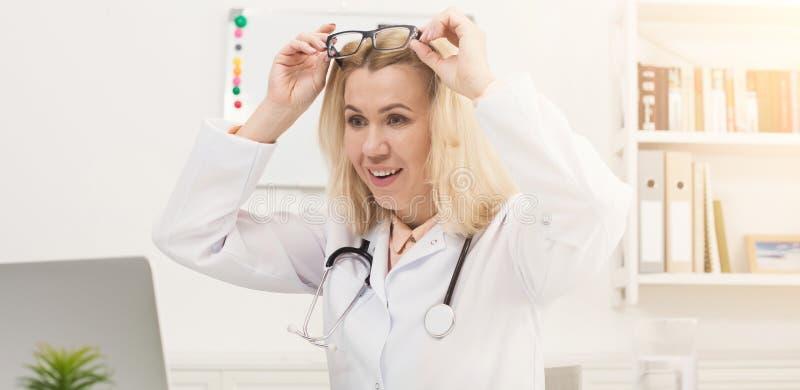 Έκπληκτος γιατρός με τα γυαλιά που κάθεται στον υπολογιστή γραφείου στοκ εικόνα