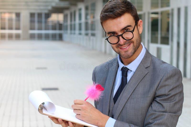 Έκπληκτος επιδεικτικός επιχειρηματίας που παίρνει τις σημειώσεις με μια χαριτωμένη ρόδινη μάνδρα στοκ εικόνα