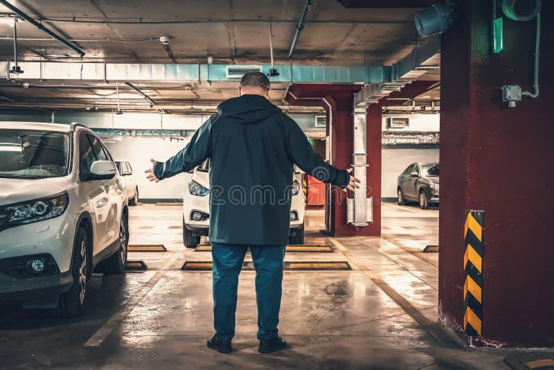 Έκπληκτος και έκπληκτος άνδρας ανακάλυψε απώλεια αυτοκινήτου σε υπόγειο πάρκινγκ Έννοια κλεμμένου αυτοκινήτου στοκ εικόνες με δικαίωμα ελεύθερης χρήσης
