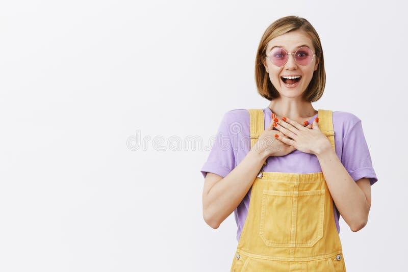 Έκπληκτος και ευτυχής όμορφος νέος θηλυκός ανθοκόμος στις κίτρινες φόρμες και τα ρόδινα γυαλιά ηλίου, που κρατούν τους φοίνικες σ στοκ φωτογραφίες με δικαίωμα ελεύθερης χρήσης