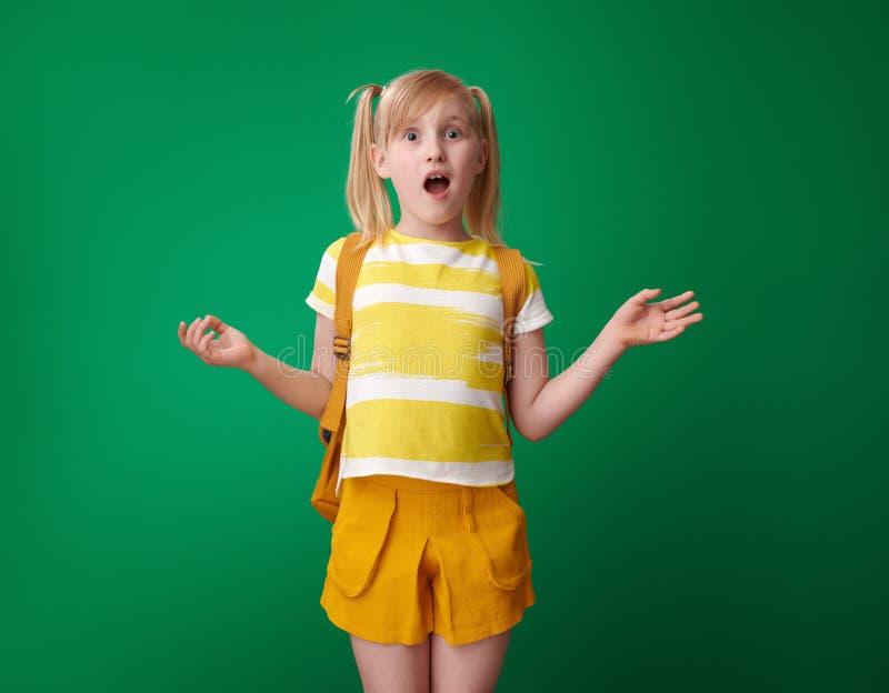 Έκπληκτος μαθητής με το σακίδιο πλάτης στο πράσινο κλίμα στοκ φωτογραφία με δικαίωμα ελεύθερης χρήσης