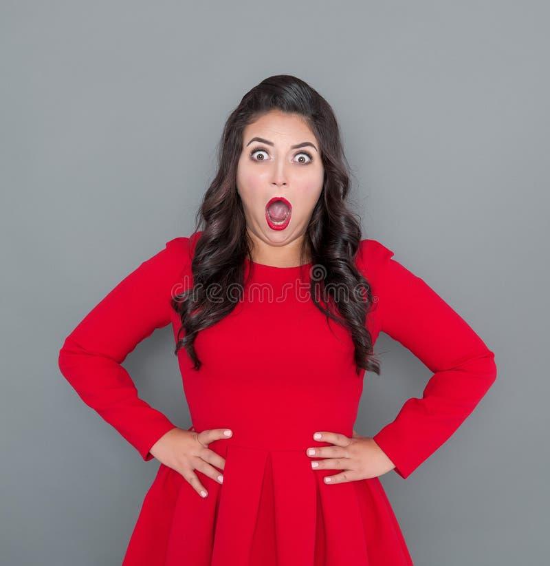 Έκπληκτος συν τη γυναίκα μεγέθους στο κόκκινο φόρεμα σε γκρίζο στοκ εικόνες
