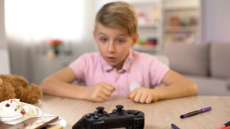 Έκπληκτο αγόρι που εξετάζει την κονσόλα, τηλεοπτικός εραστής παιχνιδιών, πρόβλημα αναβλητικότητας στοκ εικόνες με δικαίωμα ελεύθερης χρήσης