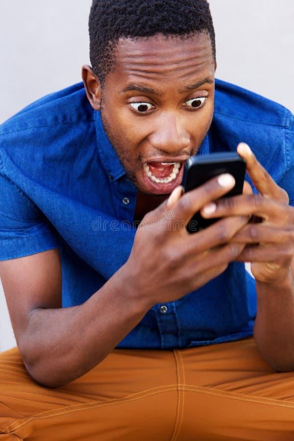 Έκπληκτο αφρικανικό άτομο που εξετάζει το κινητές τηλέφωνο και την κραυγή του στοκ εικόνες με δικαίωμα ελεύθερης χρήσης