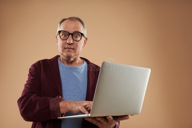 Έκπληκτο ενήλικο άτομο που εξετάζει τη κάμερα στεμένος με το lap-top στοκ φωτογραφία με δικαίωμα ελεύθερης χρήσης