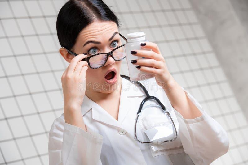 Έκπληκτο θηλυκό γιατρών με τα χέρια και τα χάπια στεμένος με το στόμα ανοικτό στο ιατρικό υπόβαθρο γραφείων στοκ φωτογραφίες