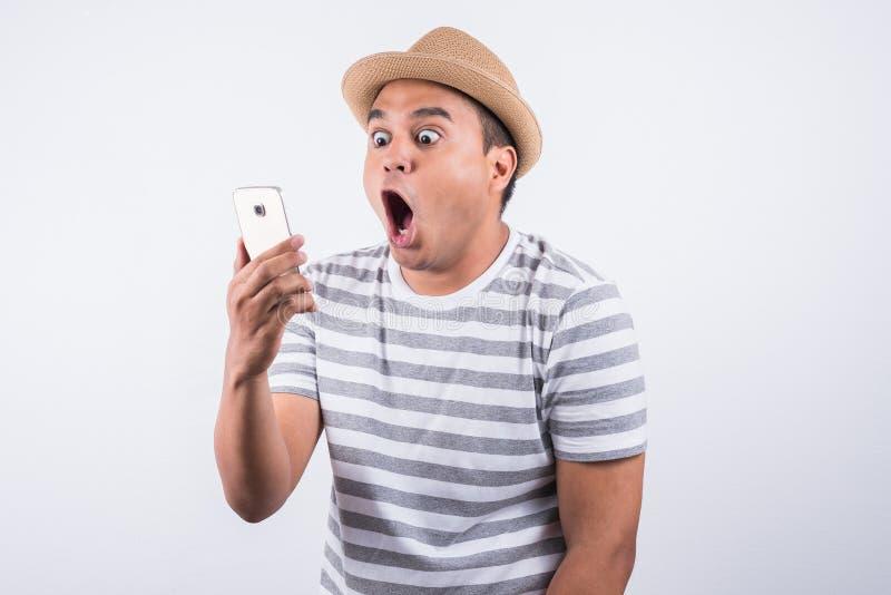 Έκπληκτο και συγκλονισμένο ασιατικό άτομο που φαίνεται smartphone στοκ φωτογραφία με δικαίωμα ελεύθερης χρήσης