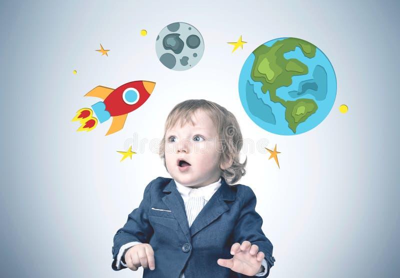 Έκπληκτο χαριτωμένο μικρό παιδί σε ένα κοστούμι, διαστημικός πύραυλος στοκ εικόνα με δικαίωμα ελεύθερης χρήσης