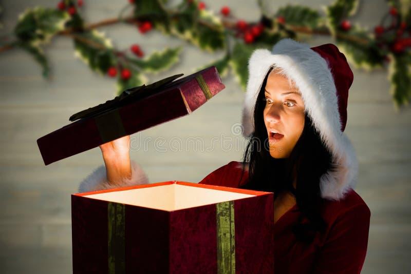 Έκπληκτη γυναίκα στο κοστούμι santa που ανοίγει ένα δώρο Χριστουγέννων στοκ φωτογραφία με δικαίωμα ελεύθερης χρήσης