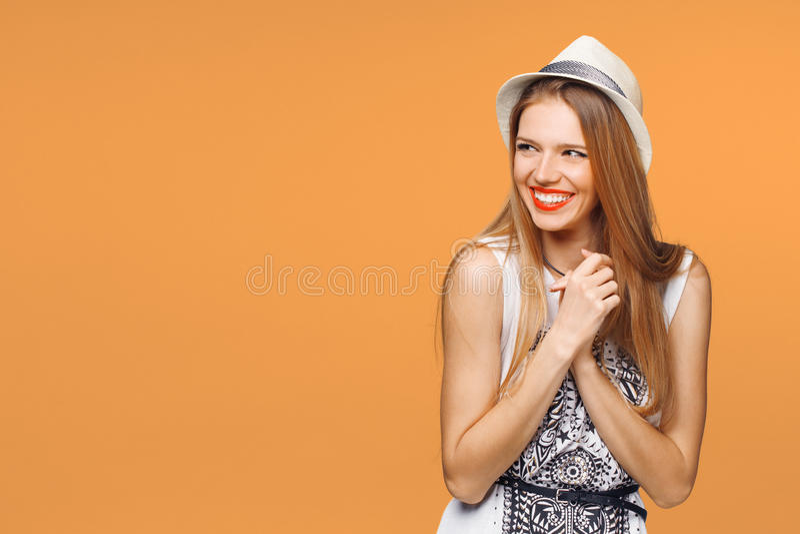 Έκπληκτη ευτυχής νέα γυναίκα που κοιτάζει λοξά στον ενθουσιασμό Απομονωμένος πέρα από το πορτοκαλί υπόβαθρο στοκ φωτογραφία