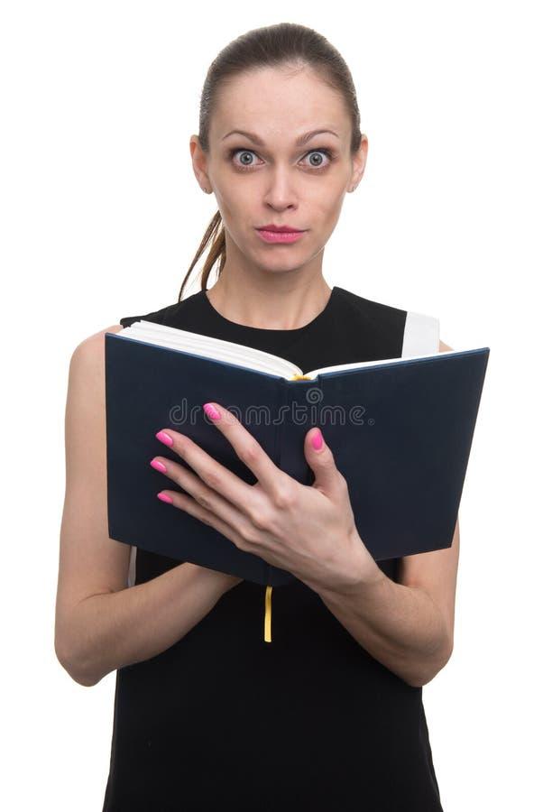 Έκπληκτη νέα επιχειρησιακή γυναίκα που εξετάζει το ημερολόγιο στοκ εικόνα με δικαίωμα ελεύθερης χρήσης