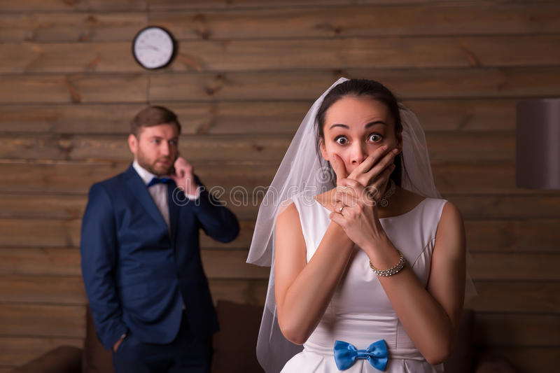 Έκπληκτη νύφη ενάντια στο νεόνυμφο που μιλά στο τηλέφωνο στοκ εικόνα με δικαίωμα ελεύθερης χρήσης