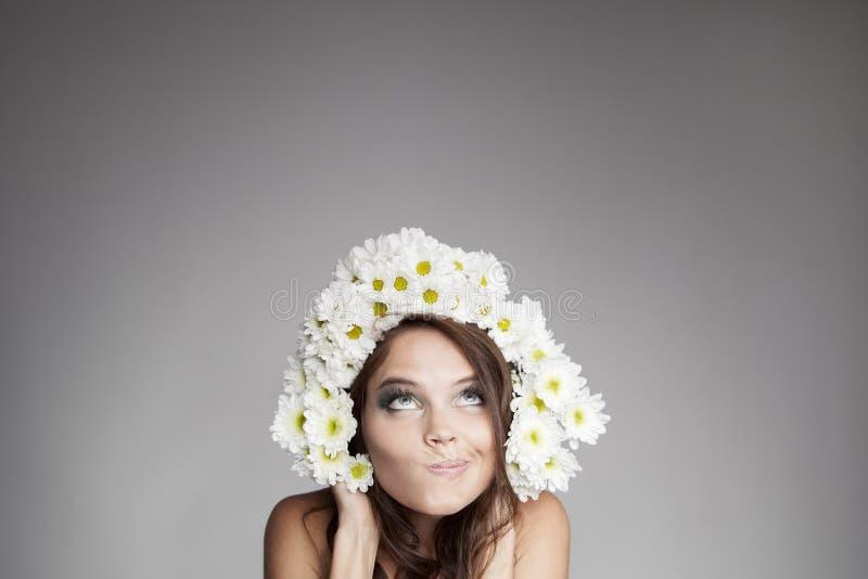 Έκπληκτη σκεπτόμενη γυναίκα με το στεφάνι λουλουδιών που ανατρέχει στοκ φωτογραφία