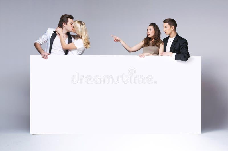 Έκπληκτοι φίλοι που κοιτάζουν επίμονα στο φίλημα του ζεύγους στοκ εικόνα