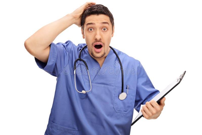 Έκπληκτος νέος γιατρός μπλε σε ομοιόμορφο στοκ εικόνες