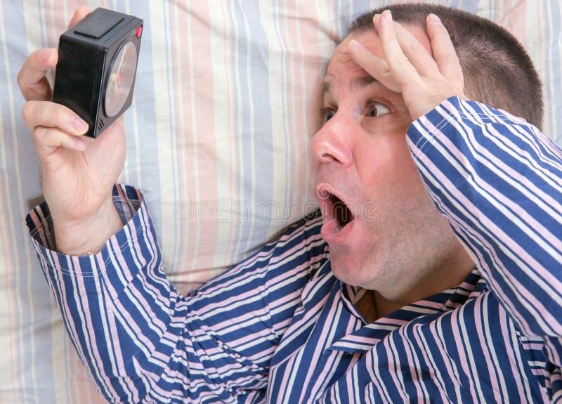 Έκπληκτο άτομο στο κρεβάτι στοκ φωτογραφία