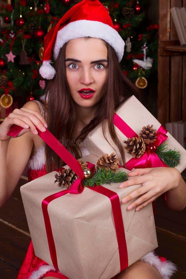Έκπληκτο κορίτσι santa στα καπέλα santa που ανοίγει το κιβώτιο δώρων christm πλησίον στοκ φωτογραφία