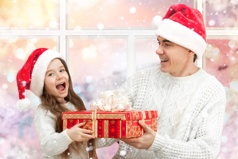 Έκπληκτο παιδί με τον πατέρα της που κρατά ένα δώρο στοκ φωτογραφία με δικαίωμα ελεύθερης χρήσης