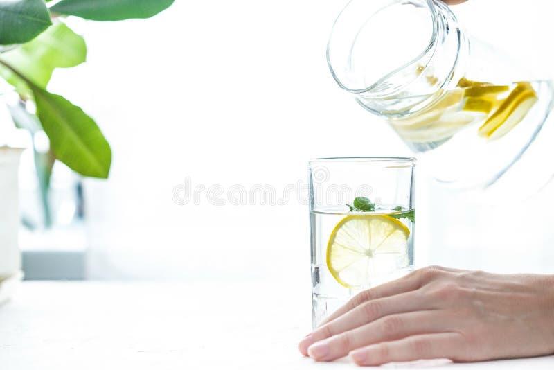 Έκχυση ενός ποτηριού του νερού με το λεμόνι, τον πάγο και τη μέντα σε έναν άσπρο πίνακα στοκ φωτογραφίες με δικαίωμα ελεύθερης χρήσης
